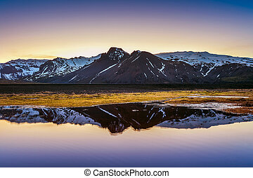 Winter mountains reflection at sunset in a lake.