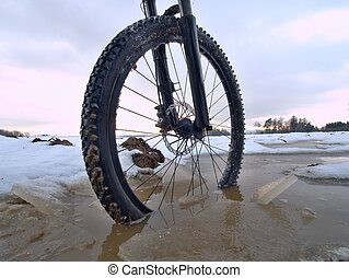 Winter mtb riding in snowy country. Low ankle view to wheel with snow mud tyre.