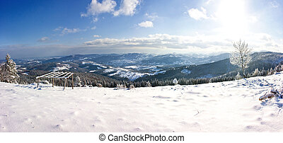 Winter panorama of mountains on a sunny day .