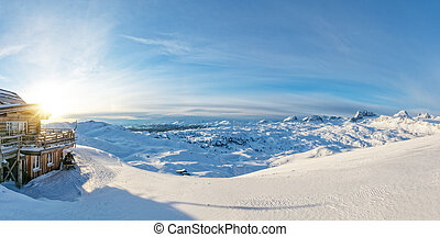 Winter panoramic view in Alps with log cabin
