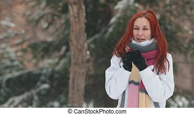 Winter park. A cheerful woman with bright red hair tries to warm up in a cold weather