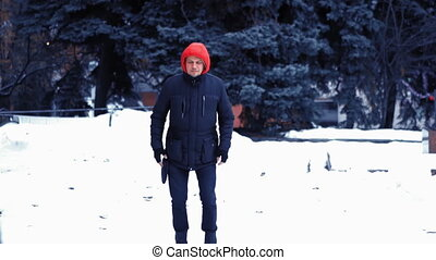 Winter Park. A man in black clothes jumps against a background of spruce. Charging outdoors. Winter fitness concept. High quality FullHD footage