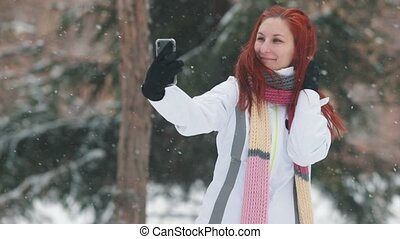 Winter park. A woman with bright red hair standing in front of snowy trees and taking a selfie
