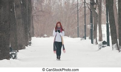 Winter park. A woman with bright red hair talking on phone