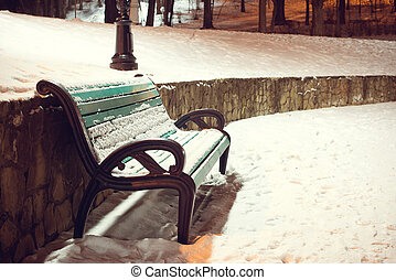 Winter park. green bench covered with snow in the evening