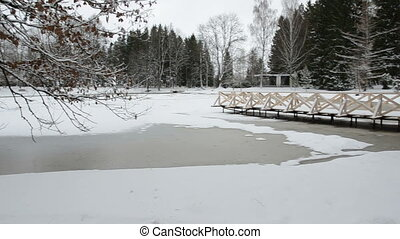 winter pond with wooden bridge - winter pond with snow and...