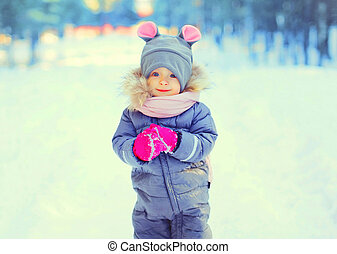 Winter portrait funny smiling child in snowy day