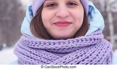 Winter portrait of a charming young woman looking at the camera