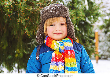 Winter portrait of a cute little boy under the snowfall, wearing warm blue jacket and colorful scarf
