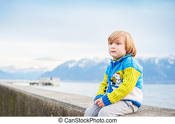 Winter portrait of a cute little boy, wearing funny warm knitted jacket with snowman, sitting by the lake against mountains