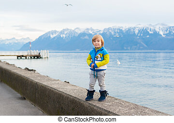 Winter portrait of a cute little boy, wearing funny warm knitted jacket with snowman, standing next to lake against mountains