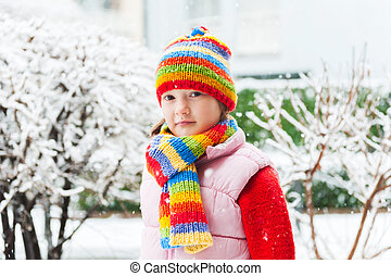 Winter portrait of a cute little girl under the snowfall, wearing red pullover, colorful hat and scarf