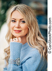 Winter portrait of beautiful woman with blond hair, wearing blue pullover