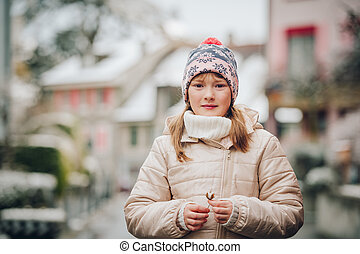Winter portrait of pretty little girl wearing warm beige jacket and hat