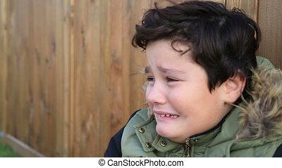Winter portrait of sad boy in warm clothes crying - Portrait...