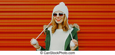 Winter portrait of smiling young woman wearing a white hat with pom pom on red background