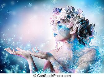 Winter portrait of woman blowing