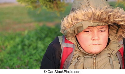 Winter portrait of young boy in warm clothes sneezing