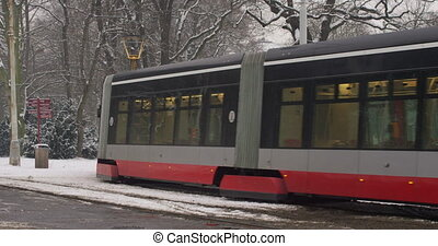 Winter public transport in Prague in the winter on a snowy day. A tram and a train passing by each other. Slow motion
