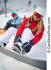 Winter recreation - Smiling female snowboarder in activewear...