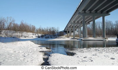 Winter river with open water under the bridge