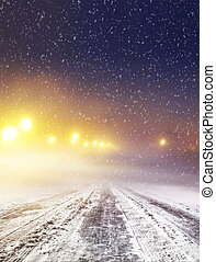 Snow covered winter road with shining streetlights at night