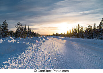 sunset over a snowy E45 in swedish lapland. The E45 is the longest road in Sweden with a length of 1,680 kilometers