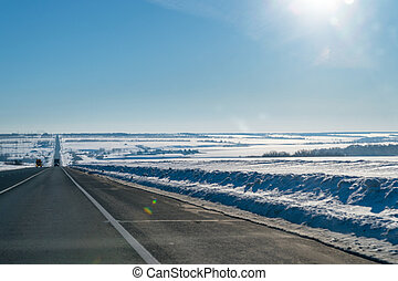 Winter road on the background of the sun in blue sky