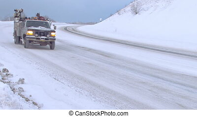 Several vehicles being driven on a snowy Alaskan road in the winter time.