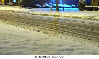 Winter road with light trails from passing cars, surrounded...