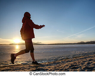 Winter running training. Middle age active person runner jogging