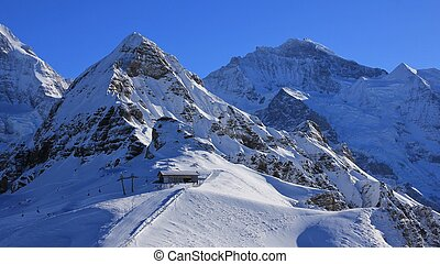 Snow covered mountains Lauberhorn and Jungfrau, summit station of a cable car