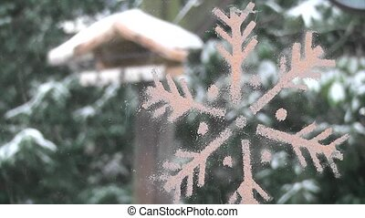 Outdoor winter garden scene with snow and a stylised snowflake decoration in the foreground for your Christmas greeting card