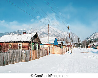 Winter scenic landscape, wooden house at the foot of snow-capped mountains
