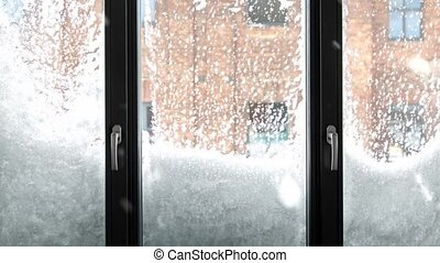 winter, season and weather concept - window covered with snow