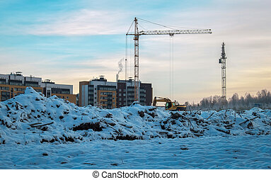 Winter season tower cranes on the construction of a buildings, in the background of the forest and all in the snow