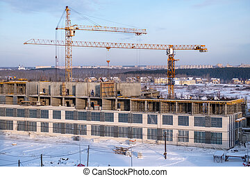 winter season tower cranes on the construction of a large building