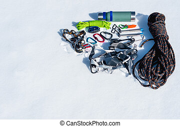 Winter set of equipment of an ice climber with carabiner wounds and a camp thermos. Copy space for the designer