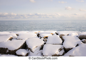 Rocks under snow on winter shore of lake Ontario in Sylvan park Toronto