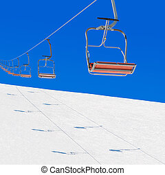 winter ski lift in snowy mountains against blue sky