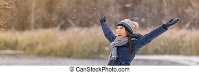 Winter snow happy woman with open arms in fun enjoying snow fall falling snowflakes wearing cold weather scarf, hat, gloves warm jacket banner panorama. Girl walking outdoor nature woods background