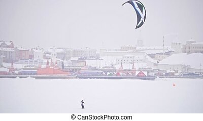 Winter Snow kiting on the ice river in front of city - extremal sport