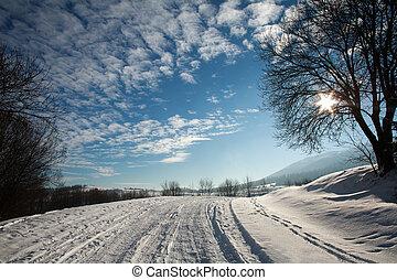 Winter snowy landscape in mountain village on blue sky