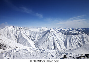 Winter snowy mountains and blue sky