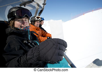 Winter sport girl in chair lift with ticket - Girl holding...