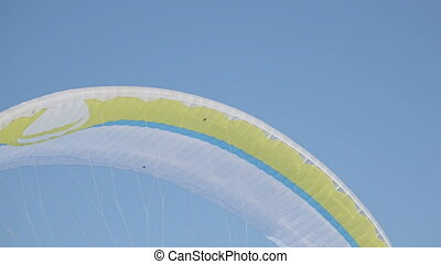 Winter sports . Bright yellow parachute against a blue sky -...