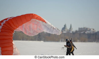 Winter sports on the freezing lake. Paragliders and...