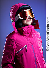 A woman in a pink winter jacket, goggles and a helmet