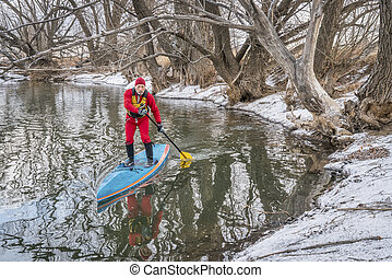 winter stand up paddling on the Poudre River in Fort...