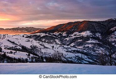 winter sunrise in mountainous rural area - beautiful warm...
